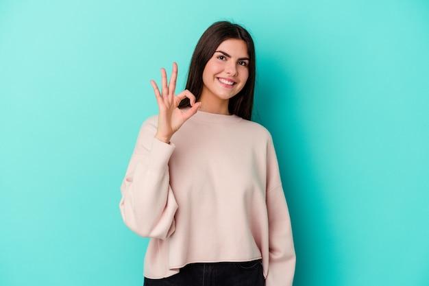Młoda kobieta kaukaski na białym tle na niebieskiej ścianie, wesoły i pewny siebie, pokazując gest ok