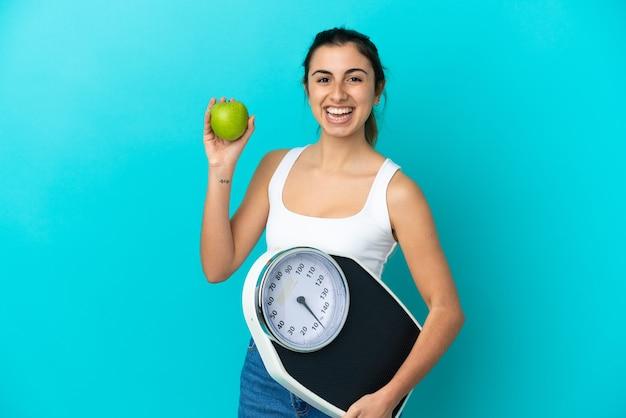 Młoda kobieta kaukaski na białym tle na niebieskiej ścianie z wagą i jabłkiem