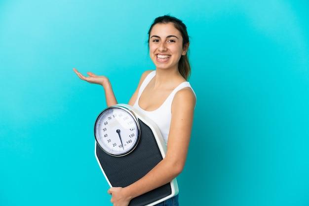 Młoda kobieta kaukaski na białym tle na niebieskiej ścianie z wagą