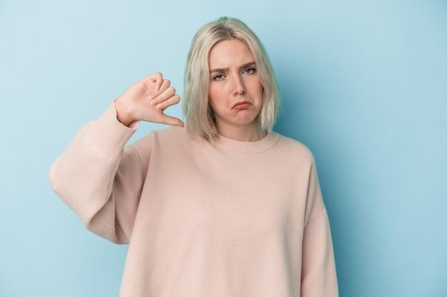 Młoda kobieta kaukaski na białym tle na niebieskim tle pokazując kciuk w dół i wyrażając niechęć.