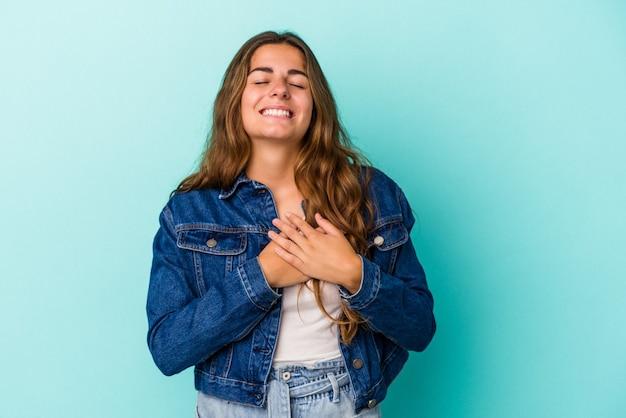 Młoda kobieta kaukaski na białym tle na niebieskim tle śmiejąc się trzymając ręce na sercu, pojęcie szczęścia.