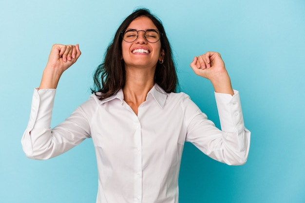 Młoda kobieta kaukaski na białym tle na niebieskim tle świętuje zwycięstwo, pasję i entuzjazm, szczęśliwy wyraz.