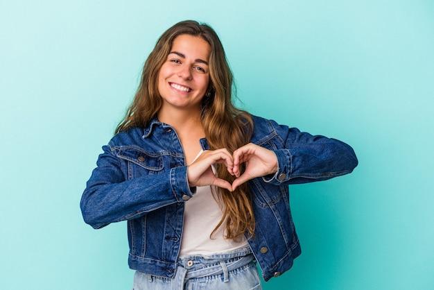 Młoda kobieta kaukaski na białym tle na niebieskim tle, uśmiechając się i pokazując kształt serca rękami.