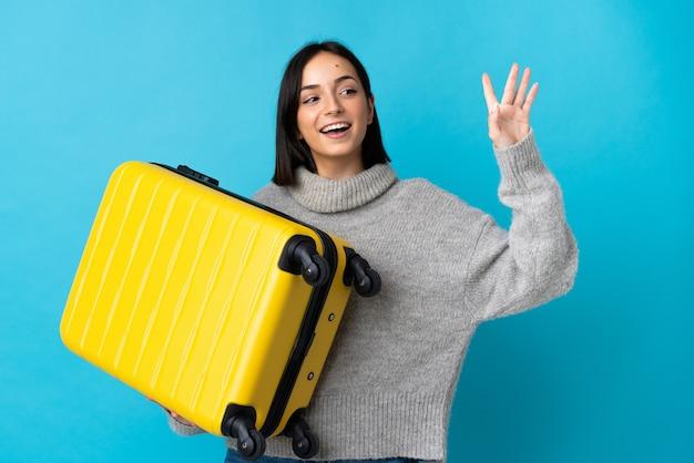 Młoda kobieta kaukaski na białym tle na niebieskim tle w wakacje z walizką podróżną i pozdrawiając