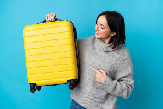 Młoda kobieta kaukaski na białym tle na niebieskim tle w wakacje z walizką podróżną