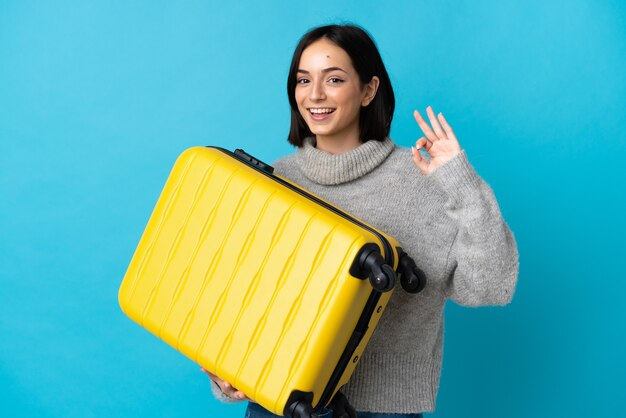Młoda kobieta kaukaski na białym tle na niebieskim tle w wakacje z walizką podróży i co znak ok