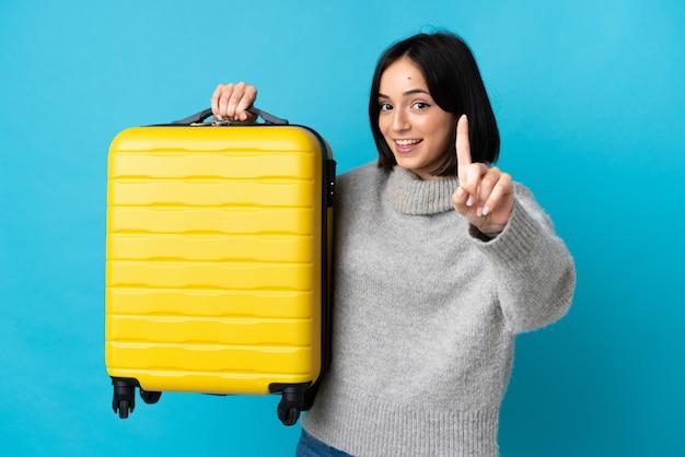 Młoda kobieta kaukaski na białym tle na niebieskim tle w wakacje z walizką podróży i licząc jeden