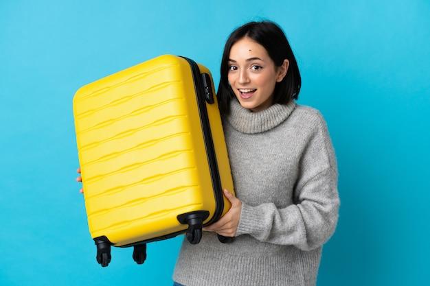 Młoda kobieta kaukaski na białym tle na niebieskim tle w wakacje z walizką podróży i zaskoczony