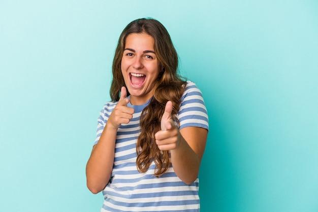 Młoda kobieta kaukaski na białym tle na niebieskim tle, wskazując do przodu palcami.