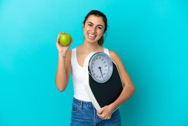 Młoda kobieta kaukaski na białym tle na niebieskim tle z wagą i jabłkiem