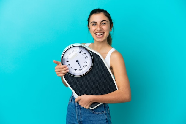Młoda kobieta kaukaski na białym tle na niebieskim tle z wagą