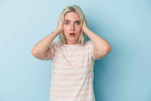 Młoda kobieta kaukaski na białym tle na niebieskim tle zakrywając uszy rękami starając się nie słyszeć zbyt głośnego dźwięku.