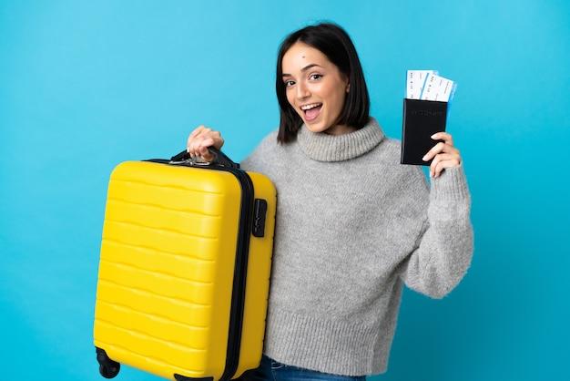 Młoda kobieta kaukaski na białym tle na niebiesko w wakacje z walizką i paszportem