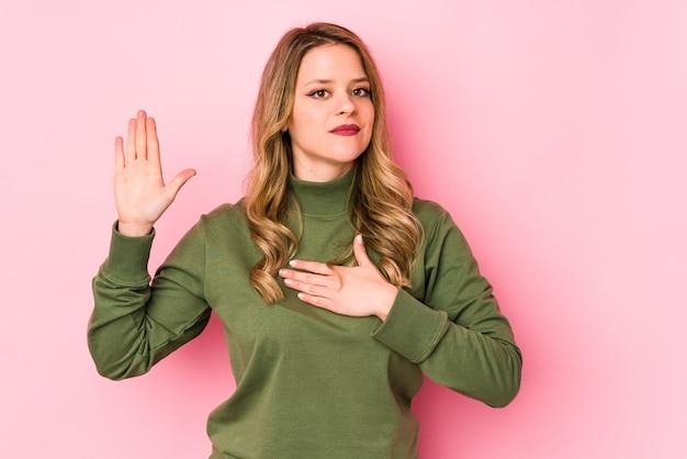 Młoda kobieta kaukaski na białym tle na różowej ścianie, składając przysięgę, kładąc rękę na piersi.