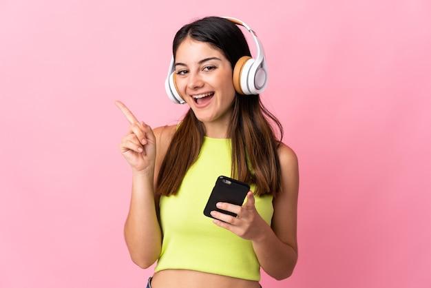 Młoda kobieta kaukaski na białym tle na różowej ścianie słuchanie muzyki z telefonu komórkowego i śpiewu
