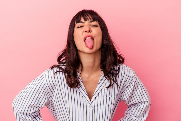 Młoda Kobieta Kaukaski Na Białym Tle Na Różowej ścianie Zabawny I Przyjazny Wystający Język. Premium Zdjęcia