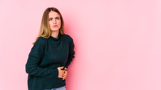Młoda kobieta kaukaski na białym tle na różowym tle ból wątroby, brzucha.