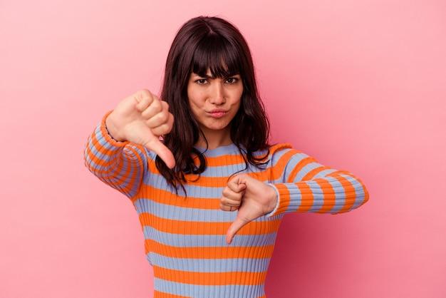 Młoda kobieta kaukaski na białym tle na różowym tle pokazując kciuk w dół i wyrażając niechęć.