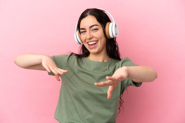 Młoda kobieta kaukaski na białym tle na różowym tle słuchania muzyki i tańca