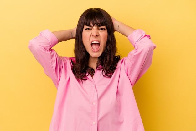 Młoda kobieta kaukaski na białym tle na żółtej ścianie krzyczy z wściekłości