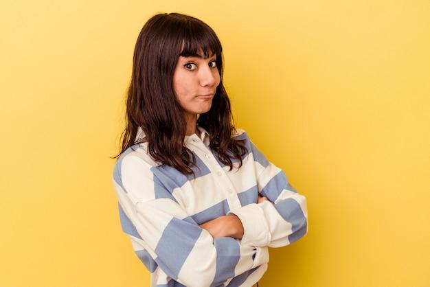 Młoda kobieta kaukaski na białym tle na żółtej ścianie niezadowolony patrząc w kamerę z sarkastycznym wyrazem.
