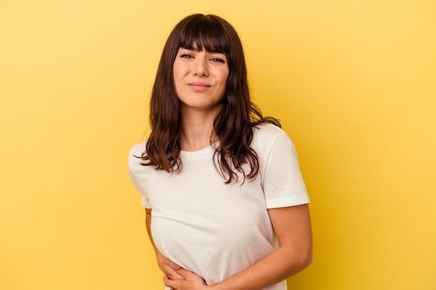 Młoda kobieta kaukaski na białym tle na żółtej ścianie o ból wątroby, ból brzucha.