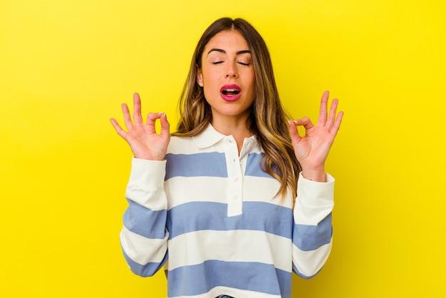 Młoda kobieta kaukaski na białym tle na żółtej ścianie relaksuje po ciężkim dniu pracy, wykonuje jogę.