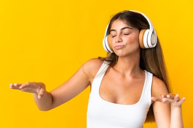 Młoda kobieta kaukaski na białym tle na żółtej ścianie, słuchanie muzyki i taniec