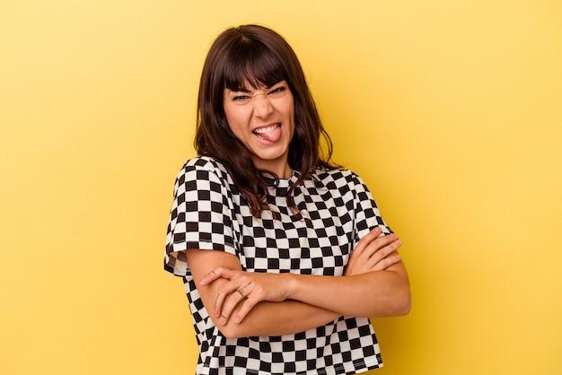 Młoda kobieta kaukaski na białym tle na żółtej ścianie zabawny i przyjazny wystający język.