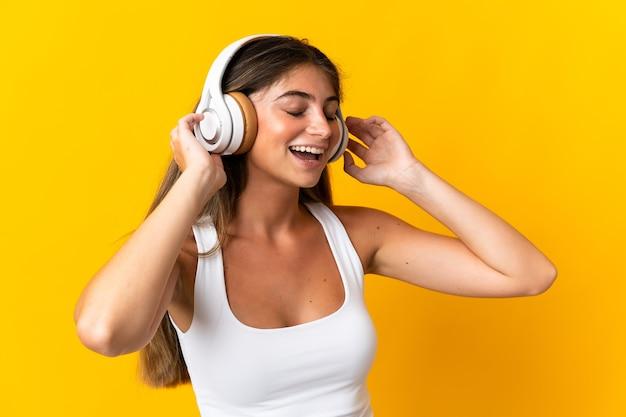 Młoda kobieta kaukaski na białym tle na żółty słuchanie muzyki i śpiewu