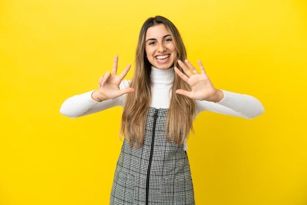 Młoda kobieta kaukaski na białym tle na żółtym tle licząc osiem palcami
