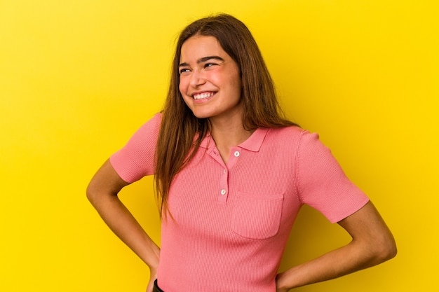 Młoda kobieta kaukaski na białym tle na żółtym tle pewnie trzymając ręce na biodrach.