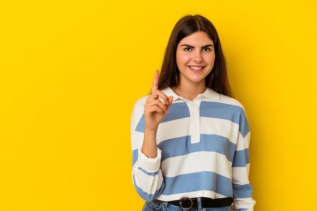 Młoda kobieta kaukaski na białym tle na żółtym tle pokazuje numer jeden z palcem.
