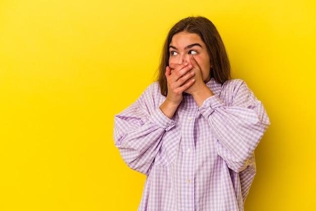 Młoda kobieta kaukaski na białym tle na żółtym tle zamyślony patrząc na miejsce obejmujące usta ręką.