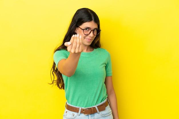 Młoda kobieta kaukaski na białym tle na żółtym tle zapraszając z ręką. cieszę się, że przyszedłeś