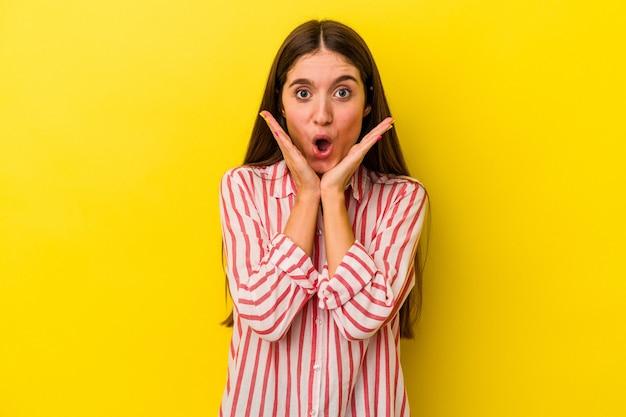 Młoda kobieta kaukaski na białym tle na żółtym tle zaskoczony i zszokowany.