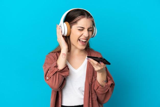 Młoda kobieta kaukaski na białym tle słuchania muzyki z telefonu komórkowego i śpiewu