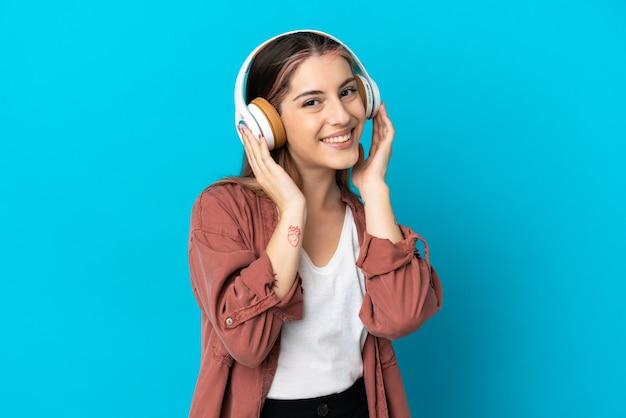 Młoda kobieta kaukaski na białym tle słuchania muzyki