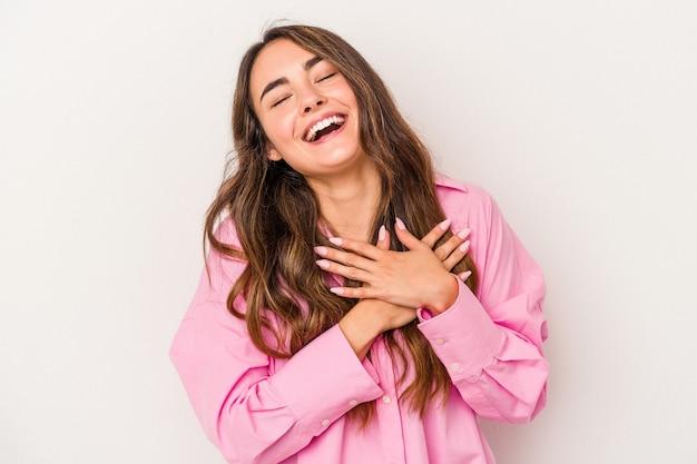 Młoda kobieta kaukaski na białym tle śmiejąc się trzymając ręce na sercu, pojęcie szczęścia.