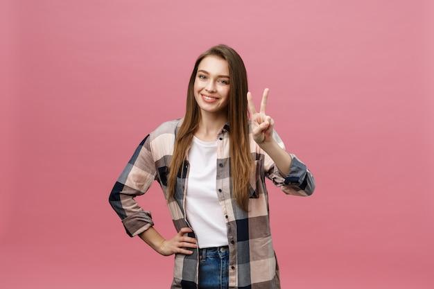 Młoda kobieta kaukaski na białym tle uśmiechając się, patrząc do kamery pokazując palce