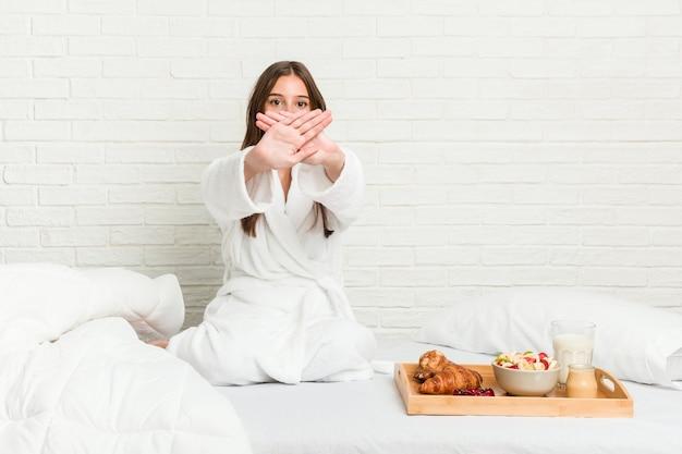 Młoda kobieta kaukaski na łóżku robi gest odmowy
