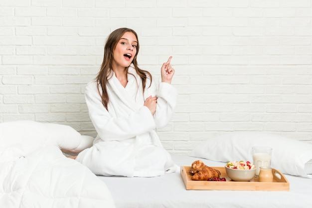 Młoda kobieta kaukaski na łóżku, uśmiechając się radośnie, wskazując palcem wskazującym z dala.