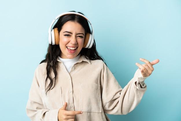 Młoda kobieta kaukaski na niebieskim tle słuchania muzyki i robi gest gitary