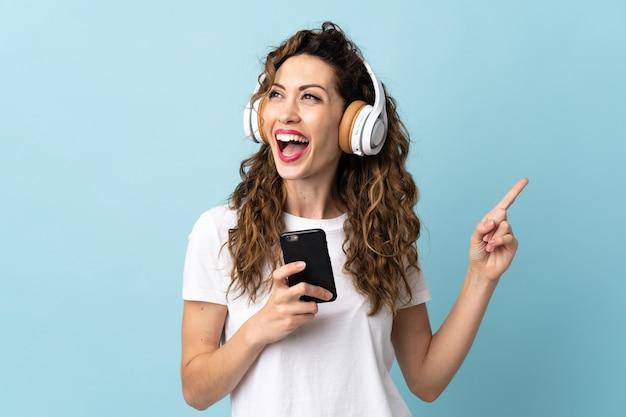 Młoda kobieta kaukaski na niebieskim tle słuchania muzyki z telefonu komórkowego i śpiewu