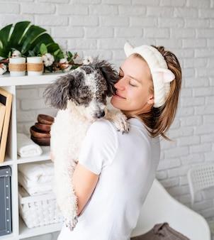 Młoda kobieta kaukaski na sobie szlafroki robi zabiegi spa ze swoim psem