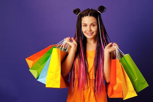 Młoda kobieta kaukaski nastolatka trzyma stos kolorowych toreb na zakupy przed fioletowym