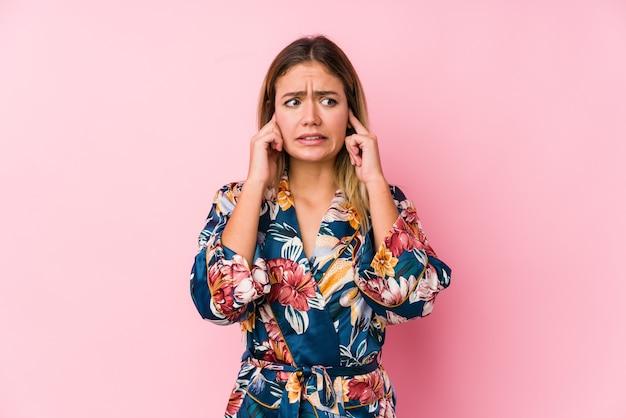 Młoda kobieta kaukaski noszenie piżamy zakrywające uszy rękami.