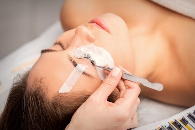 Młoda kobieta kaukaski o procedury przedłużania rzęs w gabinecie kosmetycznym. kosmetyczka przykleja rzęsy pęsetą