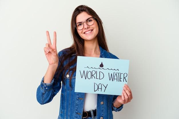 Młoda kobieta kaukaski obchodzi światowy dzień wody na różowym tle, marząc o osiągnięciu celów i zamierzeń