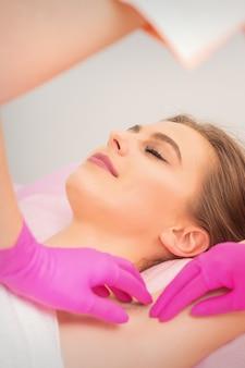 Młoda kobieta kaukaski odbiera woskowanie pod pachami rękami w rękawiczkach kosmetyczki w salonie depilacji